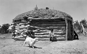 Dine' child holding an Angora goat kid with lead rope near Window Rock, AZ in 1950.