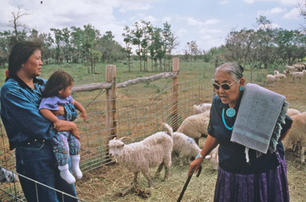 Mary Begay and her daughter, Sharon Begay, and holding her daughter at the base of Dibe'ntsa' near Fort Lewis Ag Station, at Hesperus, CO in 1995.  Mary had just completed a blessing ceremony on the flock before being turned out to start a long grazing season where lots of coyotes and bears live too.