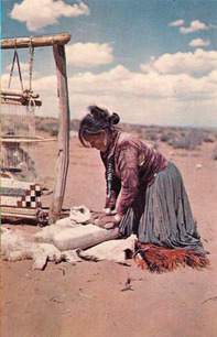 Dine' woman grinding corn on stone metate next to her weaving loom near Cameron, AZ in 1920.