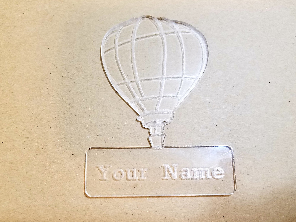 Transparent hot air balloon with name inscribed below it.