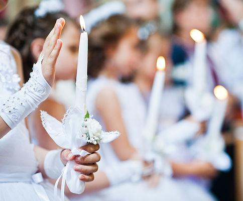 Kinder mit Kerzen bei Kommunion