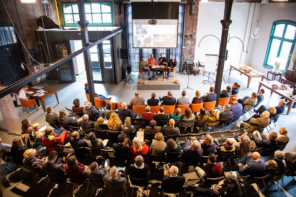 Volle zaal tijdens de talkshow op het Koplopersymposium over korte voedselketens