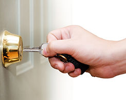 Photo of male hand putting house key int