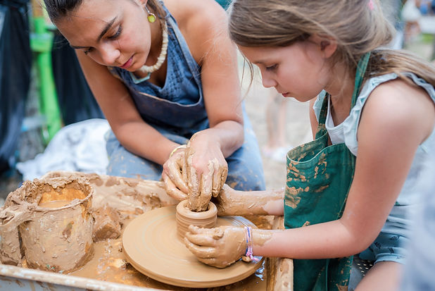 Child working with clay using pottery wh