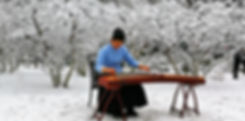 Woman is playing on a traditional chinese instrument