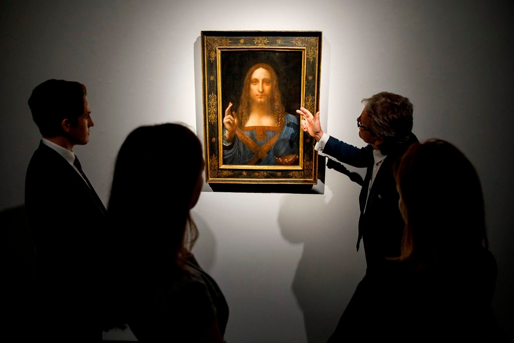 Christie's employees pose in front of Leonardo da Vinci's Salvator Mundi ahead of its sale at Christie's New York on November 15, 2017. Photo: Tolga Akmena/AFP/Getty Images.