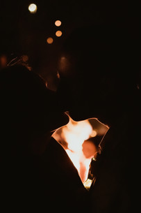 bride and groom kissing in front of bonfire