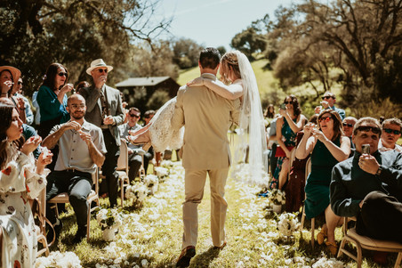 groom carrying bride in arms down the aisle after eloping