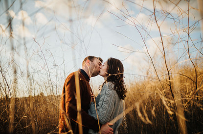 engaged couple standing and kissing in a field of tall grass at sunset in san luis obispo