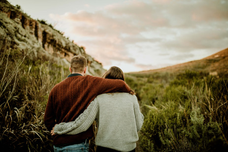 Engaged couple walk down a trail with their arms wrapped around each other at sunset