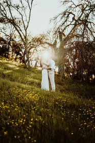 bride and groom kissing at sunset in a field of wild flowers