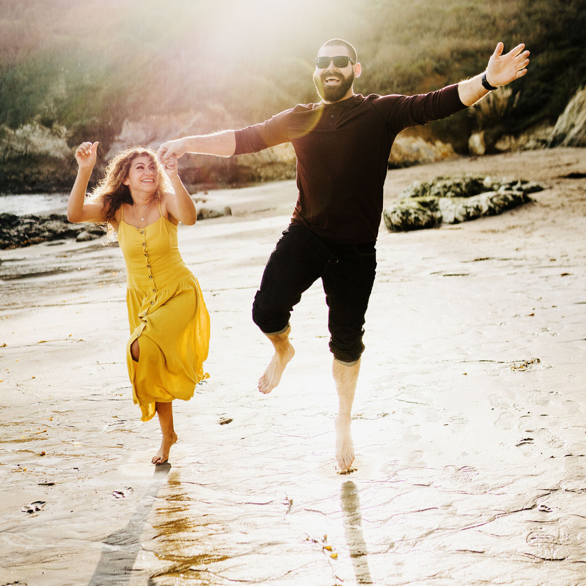 engaged couple leap into the air holding hands in celebration of their engagement along the coast of san luis obispo
