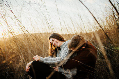 engaged couple snuggle up and laugh in a field of tall grass at sunset in san luis obispo