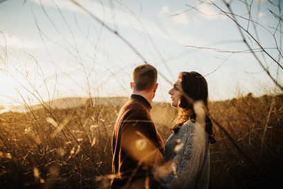 engaged couple standing in a field of tall grass at sunset in san luis obispo