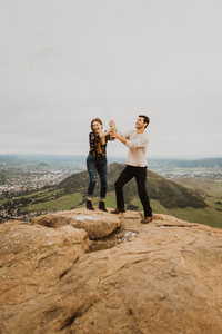 couple popping a bottle of champagne on the top of bishops peak, san luis obispo, california, to celebrate their engagement