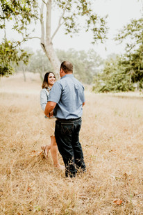 engaged couple dancing and smiling under in a field of grass at the alisal guest ranch and resort