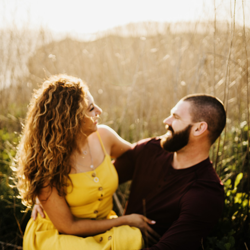 engaged couple cuddle in a field of tall grass laugh and smile at each other madly in love along the coast of san luis obispo