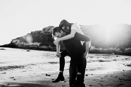 engaged couple playing tag, laughing, and smiling along the beach in san luis obispo