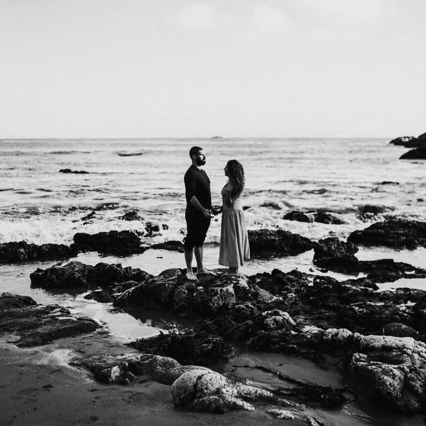 engaged couple hold hands while standing on a rock in san luis obispo