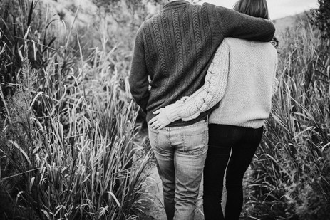Engaged couple walking down a trail with their arms wrapped around each other