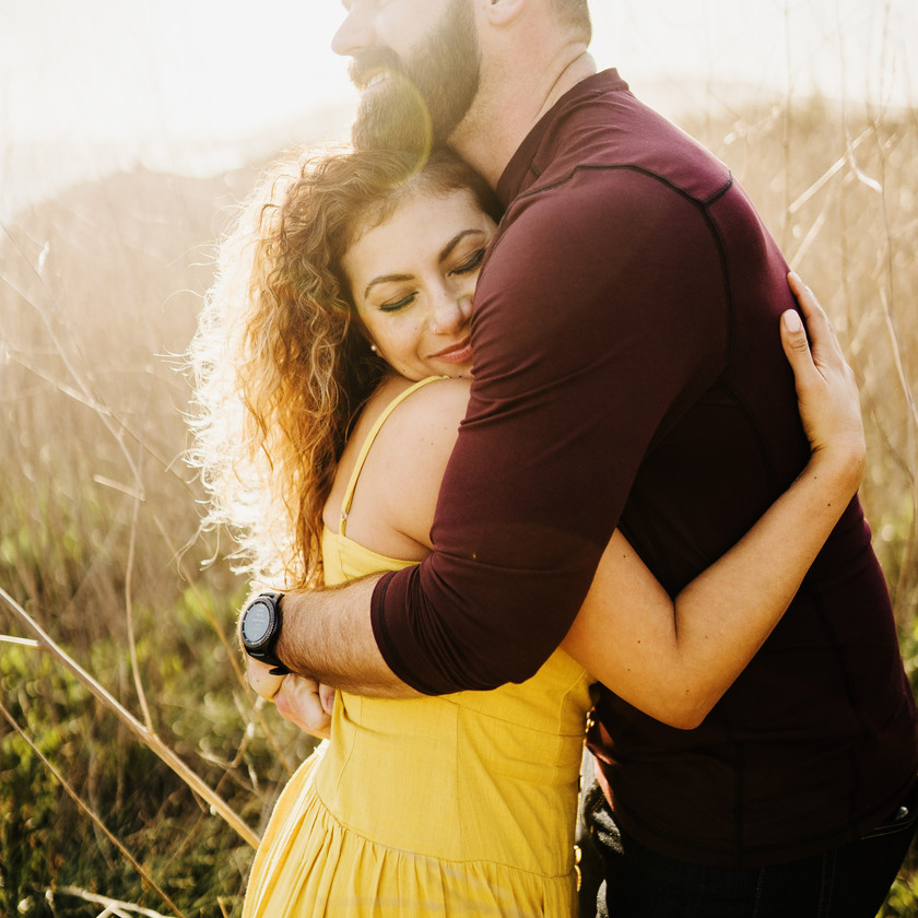 engaged couple share a warm hug in a field of tall grass along the coast of san luis obispo