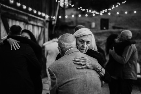 grandmother and grandfather hugging during reception