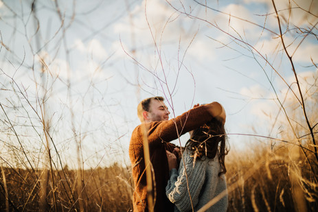 engaged couple dancing and playing in a field of tall grass at sunset in san luis obispo
