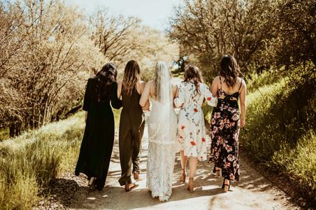 bridal party walking down a road