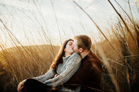 engaged couple snuggle up and kiss in a field of tall grass at sunset in san luis obispo