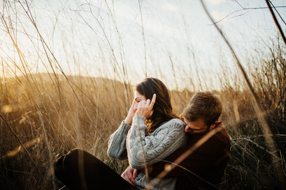 engaged couple snuggle up in a field of tall grass at sunset in san luis obispo