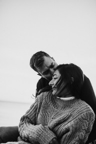 man kissing woman on the forehead while woman smiles during engagement shoot