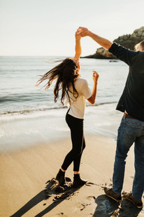 engaged couple dancing along the beach at sunset in san luis obispo
