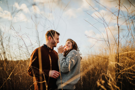 engaged couple laughing and smiling in a field of tall grass at sunset in san luis obispo