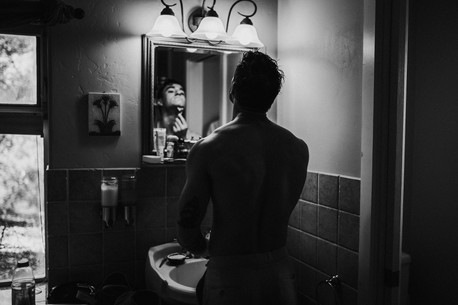 groom shaving in front of mirror before ceremony