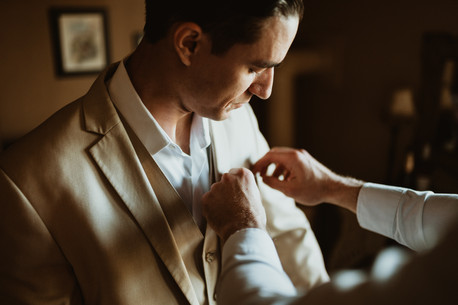grooms father helping groom with attire