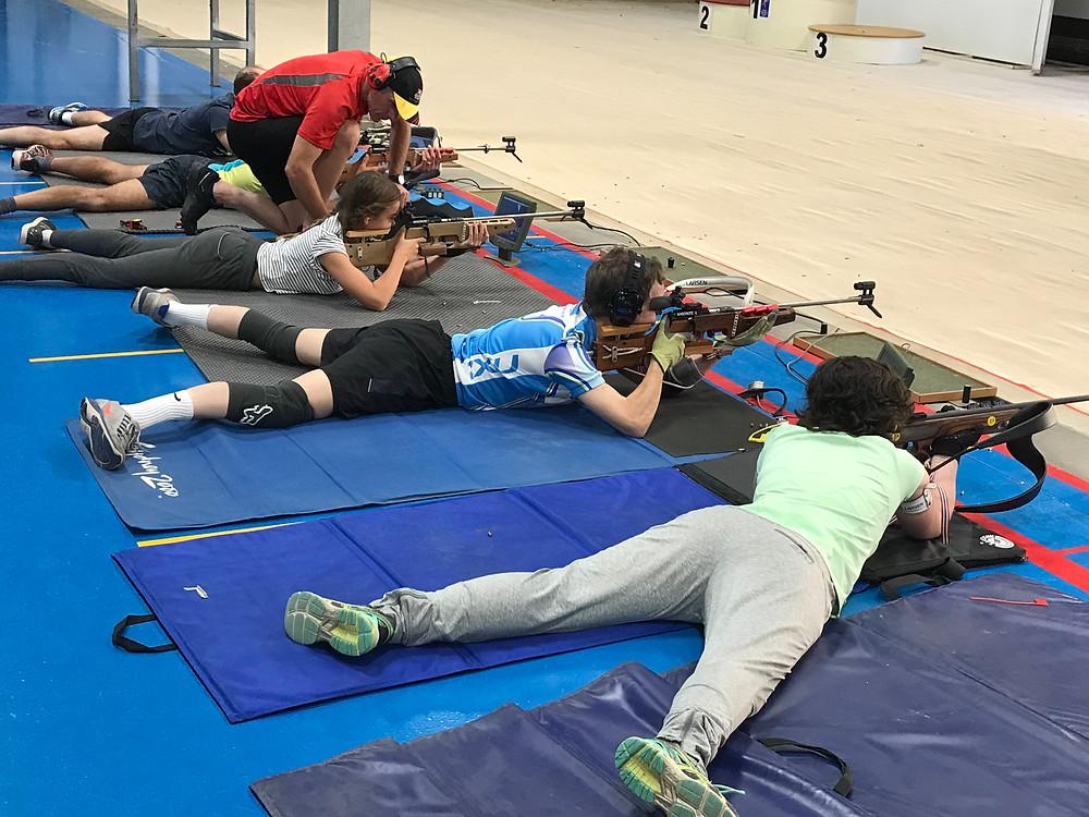 Biathletes practising target shooting in the prone position