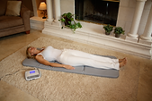 Woman lying on full-body Mat with Control Unit nearby. Compatible with adults, children, and pets.