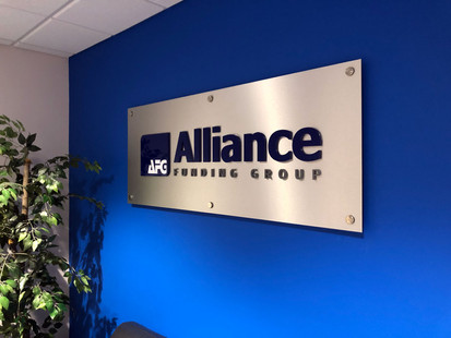 Brushed aluminum panel with dimensional letters mounted to wall with stainless steel stand-offs.
