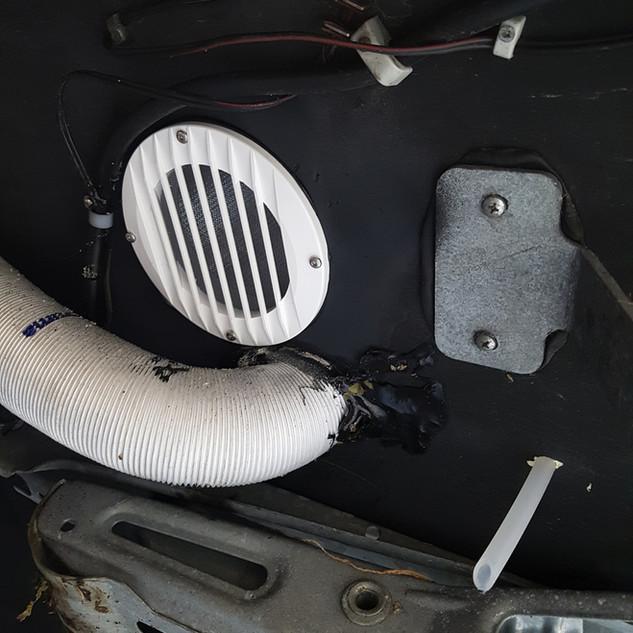 Ansicht von unten. Über das weisse Gitter wird die Abwärme geleitet und beim Silikonschlauch tropft das Kondenswasser heraus.
