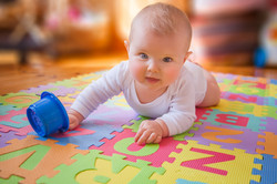 Blue-eyed reaching for cup on alphabet mat during tummy time.