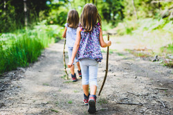 Children - identical twins girls are hiking in the mountains. Active family, parents and children mo