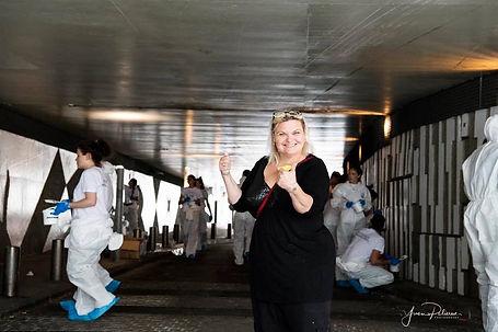Photo de Sylvie Sanchez en train de faire le signe super, on voit derrière les employés de L'Oreal en train de peindre le passage Louis Vion