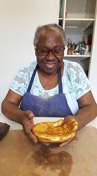 Photo d'une femme non-voyante souriante montrant une sculpture en forme de main ouverte dorée
