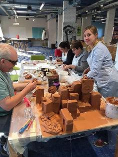 Photo de Didier Roulé et Juliette Paul en train de faire une sculpture collective avec des salariés