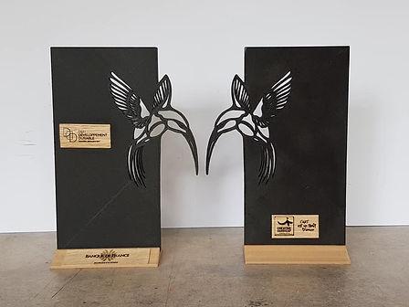 Photo de deux trophées pour la banque de france avec un oiseau découpé dans une plaque