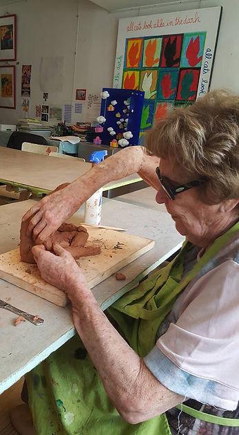 photo d'une femme aveugle qui fait de la sculpture