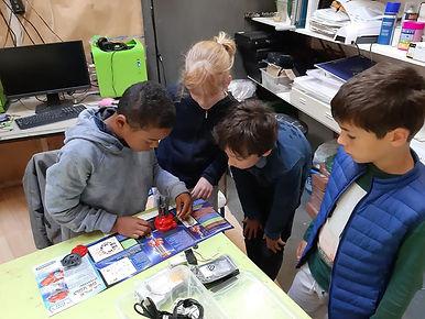 Photo de quatre enfants en train de fabriquer un robot