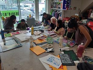Photo d'un cours d'art plastique: sept personnes sont en train de peindre autour d'une table