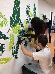 Photo de deux personnes en train de peindre la fresque