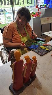 Photo d'une femme en fauteuil roulant paignant sa sculpture